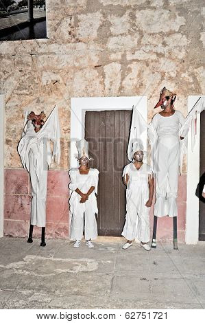 People standing on peg legs dressed in scary costumes