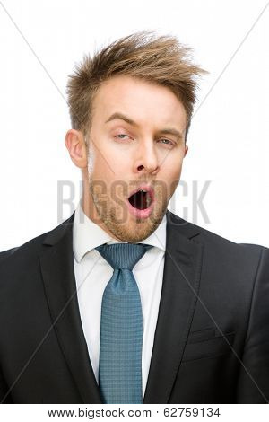 Frontal view of yawing businessman, isolated on white. Concept of tiredness and stress