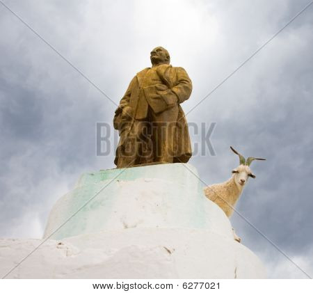 The Statue Of Lenin In The Altai Village And A Herd Of Goats On It