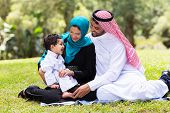cheerful muslim family sitting outdoors poster