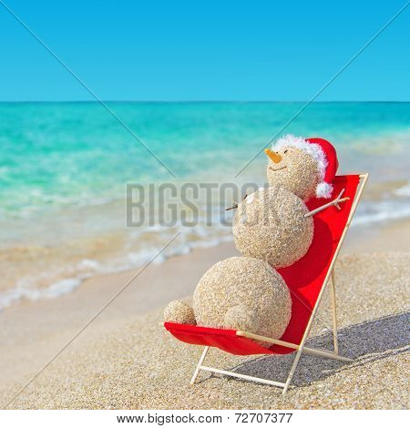 Sandy Snowman In Santa Hat Sunbathing In Beach Lounge. Holiday C