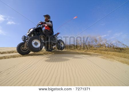 Quad Rider Cornering In Rippled Sand Dunes