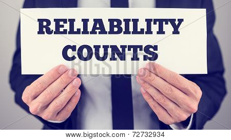 Man Holding Sign Reading Reliability Counts