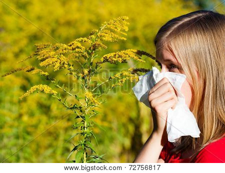Young woman blowing nose in handkerchief because of allergy. poster