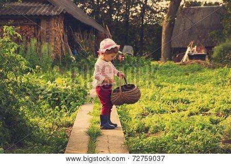 Cute kid with big basket having fun at countryside