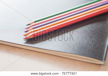 Closeup Color Pencils On Black Notebook