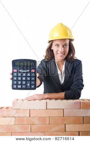 Woman construction worker with calculator on white