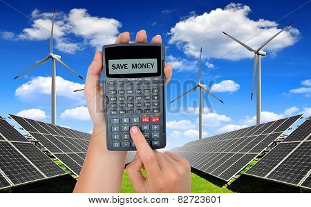 Hand with calculator. In the background solar energy panels and wind turbines