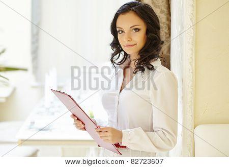Friendly restaurant hostess posing at camera