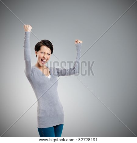Beautiful girl yes gesturing is happy, isolated on grey