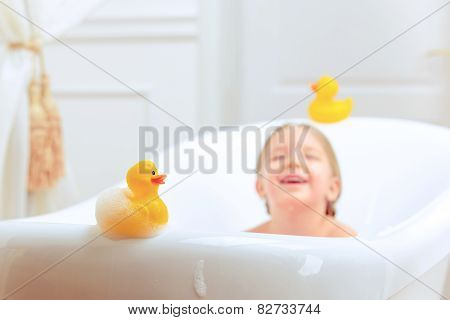Bath time is fun. Selective focus image of a cute little girl taking a bath and playing with rubber ducks while sitting in a luxurious bathtub poster