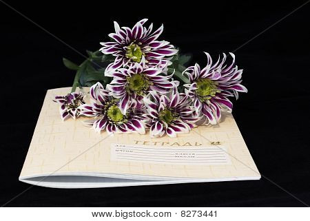 Closed Notebook And Flowers