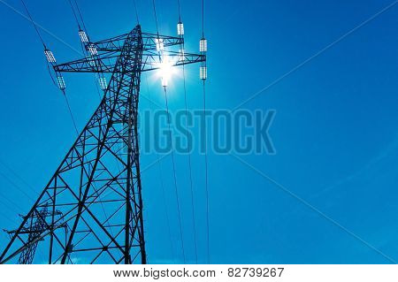 the power pole high-voltage lines with sun and blue sky. energy supply by power line. poster