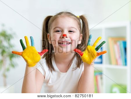 cute kid child showing her hands painted in bright colors