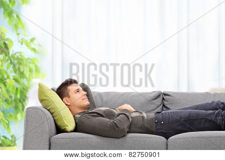 Relaxed young man lying on a sofa at home