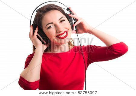 Girl In Long-sleeve T-shirt Wearing Red Lipstick Touching Big Headphones Listening To Music Smiling