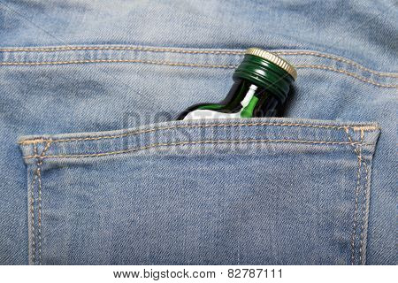 alcoholism concept - bottle with alcohol in back pocket of blue jeans poster