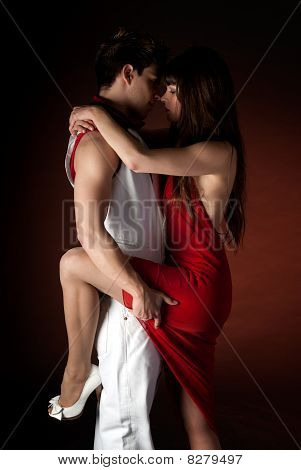 Young Couple Dancing Embrace Passion Romance On Dark Red Light Background.