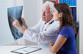 Senior physician showing rtg to his patient poster
