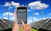Hand with calculator. In the background solar energy panels and wind turbines.Concept of saving money. poster