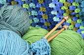 Yarn crafts, wool in blue and green , crochet afghan blanket, wooden knitting needles poster