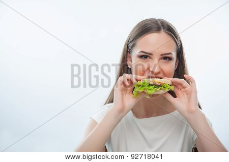 Beautiful young girl is eating unhealthy food