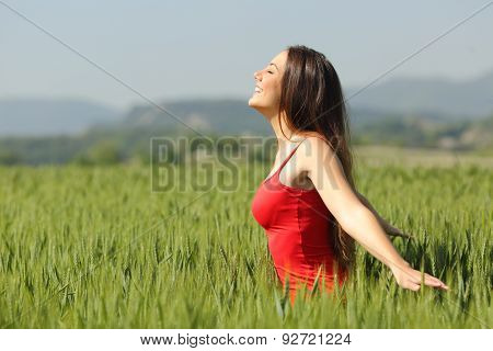 Woman Breathing Fresh Air In A Meadow And Touching The Wheat