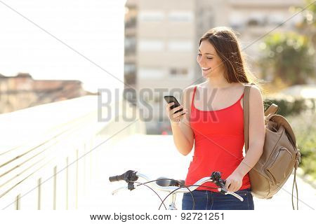 Woman Using A Smart Phone Walking With A Bicycle