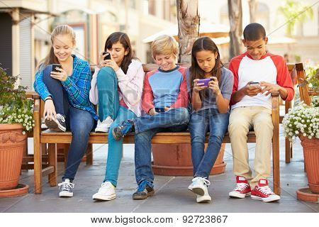 Group Of Children Sitting In Mall Using Mobile Phones