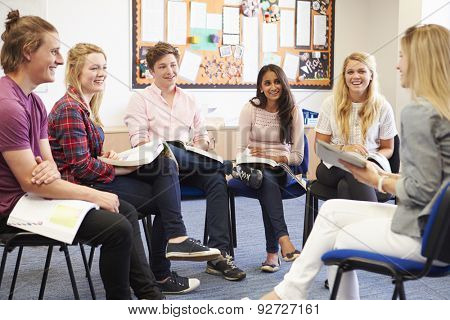 College Students With Tutor Having Discussion