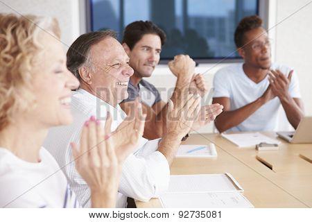 Businesspeople Applauding Colleague In Boardroom