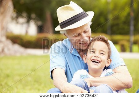 Grandfather And Grandson Sitting In Park Together