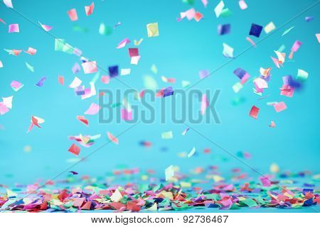 Colored confetti flying on blue background