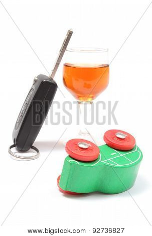 Overturned Model Vehicle, Glass Of Wine And Car Key. White Background