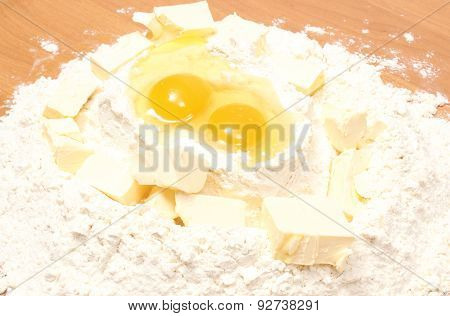 Broken Eggs In Flour And Cube Of Margarine Lying On Table