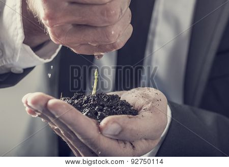 Businessman Pouring Water Over A Young Green Plant Held In His Hand
