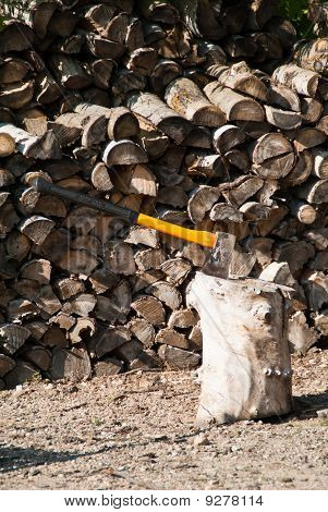 A Yellow Axe Used For Chopping Firewood With Blade In  Chopping Block