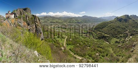 Panorama of the mountains and a small temple at the top. Caucasus. Karachay-Cherkess Republic.