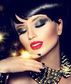 Beauty Fashion Model Girl with bright Makeup and golden Accessories. Rocker Style Brunette Portrait. Short haircut. Fringe Hairstyle. Rocker or Punk sexy Woman. Isolated on black background. Hair cut poster
