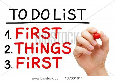 Hand writing First Things First in To Do List with red marker isolated on white.