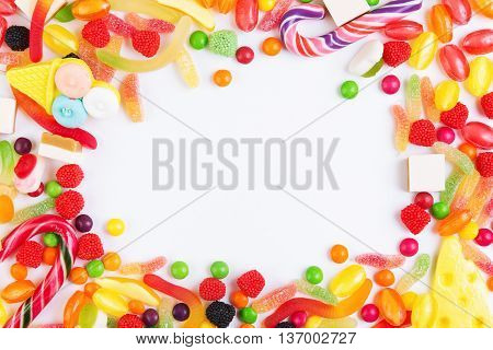 Colorful candies jellies and lolly pops arranged as frame with copy space. Top view