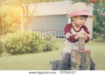Asian farmer boy riding on a wooden toy trucker.