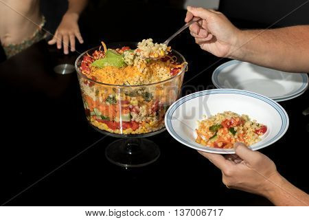 Woman serving child a plate of Multi Layered Salad in a Glass Trifle Bowl on black background
