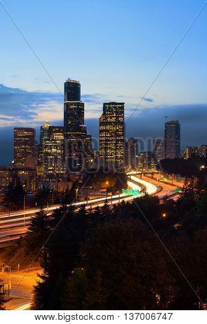 Seattle city view with urban architecture and traffic light trail at dusk.