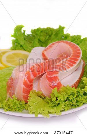 Uncooked Fresh Salmon Bellies decorated with salad and lemon slices isolated on white background