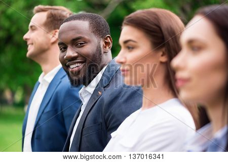 Full of emotions. Close up of positive handsome man smiling and expressing joy while standing outside with his colleagues