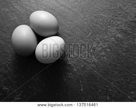 Black and white photo of brown eggs on slate