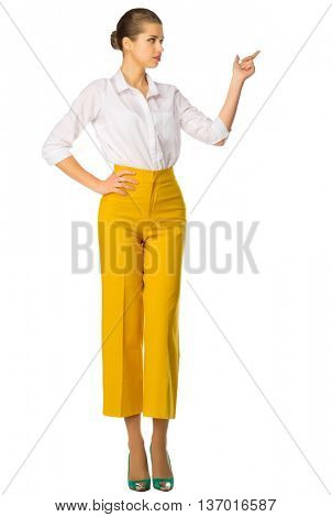 Young woman in yellow pants shows pointing gesture