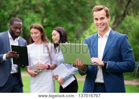 Modern user. Positive handsome joyful man using laptop and expressing joy while his colleagues standing in the background