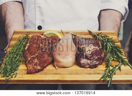 Chef holds fresh steaks ready for BBQ cooking - pork, beef and chicken. Raw meat on a cutting board with rosemary leaf. Raw pork meat on wood, closeup. Marinated in spices raw steak for barbecue.